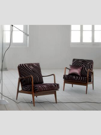 Lizzo -  Mimic Fabric Collection - Armchairs with smooth brown wood frames and seat cushions with a purple and grey fingerprint or animal stripe pattern, and a purple cushion