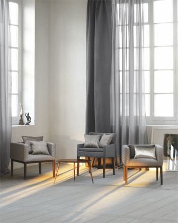 Lizzo -  Mimic Fabric Collection - Lightweight grey curtains with solid grey curtains, low-backed grey armchairs, grey and silver cushions, and a small round wood coffee table