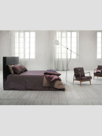 Lizzo -  Mimic Fabric Collection - Bed with black headboard, purple blanket, purple and beige throws and cushions, white anglepoise floor lamp, and patterned, wooden armchairs