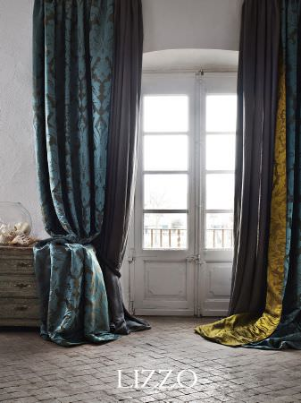 Lizzo -  Opera Fabric Collection - Long blue floral patterned fabric, with a fold of lime green floral fabric and plain mauve fabric, with cabinet and glass bowl of sea shells
