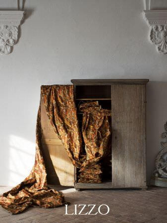 Lizzo -  Opera Fabric Collection - Grey wood cupboard with plain doors, little detail, draped with Autumn coloured patterned fabric, filled with cushions with the same pattern