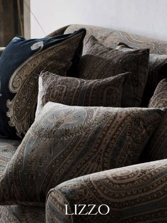 Lizzo -  Opera Fabric Collection - Midnight blue cushion with embroidered grey paisley shape, with sofa and cushions in detailed blue, cream and grey patterned fabric