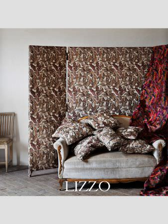 Lizzo -  Opera Fabric Collection - Off-white armchair with wood trim, with multicoloured abstract fabric, and a screen and scatter cushions with white and beige butterflies