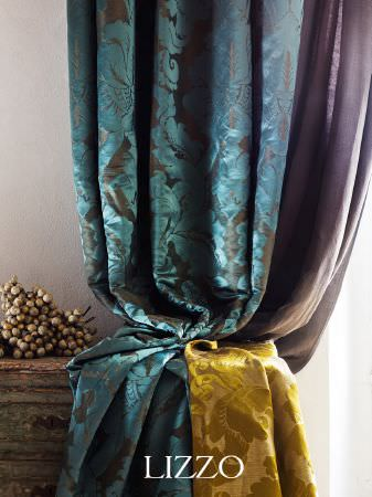 Lizzo -  Opera Fabric Collection - Sky blue and lime green fabrics with a floral pattern in two different textures, beside solid purple-grey fabric, and a rustic wooden chest