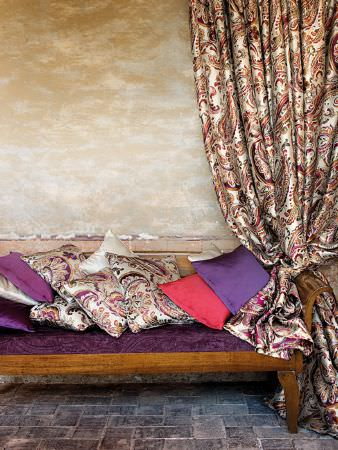 Lizzo -  Paisley Fabric Collection - Brown bench with purple seat cushion, silky white fabric with pink and purple paisley print, matching cushions, and pink and purple cushions