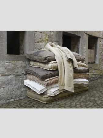 Lizzo -  Provenza Fabric Collection - Stack of rectangular seat cushions for benches in plain grey, cream, beige, white and olive green fabrics, with a plain cream blanket