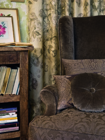 Lizzo -  Provenza Fabric Collection - Dark brown patterned seat cushion on dark grey armchair, with matching brown and grey scatter cushions, beside a solid wood shelving unit