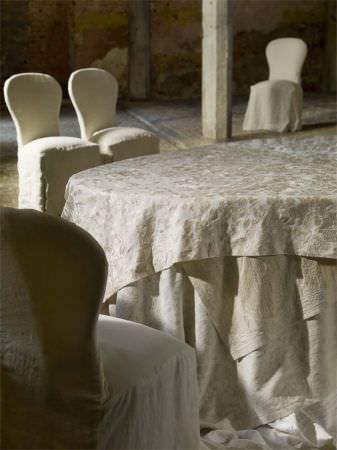 Lizzo -  Provenza Fabric Collection - Padded chairs with rounded backs, covered in plain cream seat covers, with tablecloths in subtly patterned cream muslin effect fabric