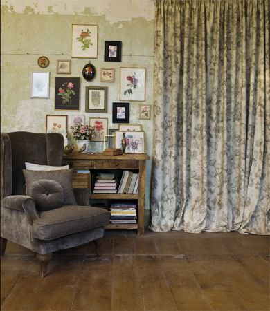 Lizzo -  Provenza Fabric Collection - Large armchair with round cushion, both dark grey, with grey and white cushions, floral curtains, rustic wood storage unit, picture frames