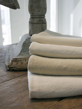 Lizzo -  Stonewash Fabric Collection - Pile of off-white and cream woven blankets on a rustic wood table, with the base of a stone urn