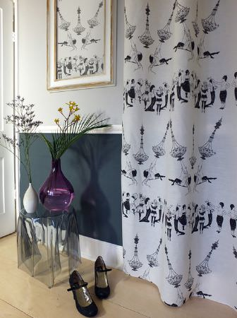 Louise Body -  Collection One Fabric Collection - Black, white and grey patterned floor-length curtains with a small perspex table, purple and white vases, and black shoes