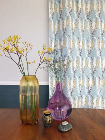 Louise Body -  Collection One Fabric Collection - A large wooden table with vases in yellow, purple and silver, with pale blue, green and white floral patterned curtains