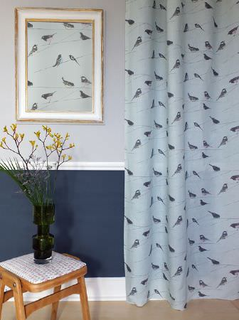 Louise Body -  Collection One Fabric Collection - Light blue and grey bird print framed artwork and matching curtains, next to a small padded wooden stool and a black vase