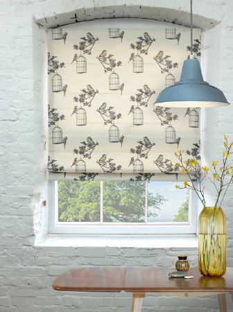 Louise Body -  Collection One Fabric Collection - A wood table with a large yellow vase, a blue hanging ceiling light, and a cream and grey birdcage print window blind