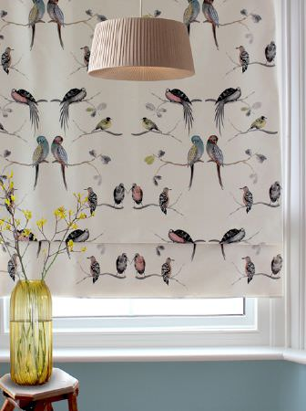 Louise Body -  Collection One Fabric Collection - Birds printed on a white window blind, with a wafer coloured ceiling lightshade, with a small wood table and a yellow vase