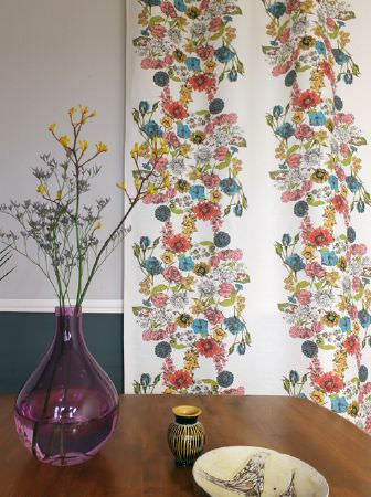 Louise Body -  Collection One Fabric Collection - A multicoloured floral patterned backdrop to a wood table with a large purple vase, a plate, and a small black and gold pot