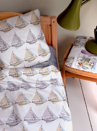 Louise Body -  Kids Fabric Collection - Beige and pale grey boats printed on white bedding, with a wooden frame, a small padded stool and an olive green lamp