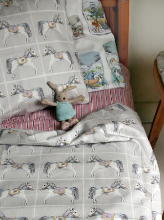 Louise Body -  Kids Fabric Collection - Wood bed with light red and white sheets, and pale grey and white horse print bedding, a jar print cushion, and a toy rabbit