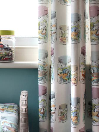 Louise Body -  Kids Fabric Collection - Creature-filled jars printed in pale colours on long white curtains beside a light woven padded seat and a jar of toys