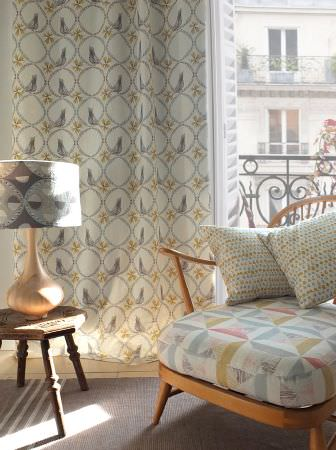 Louise Body -  Peggy Fabric Collection - Grey, cream and gold patterned curtains, a wooden chair with a large padded seat, a brown table, and a gold and grey lamp