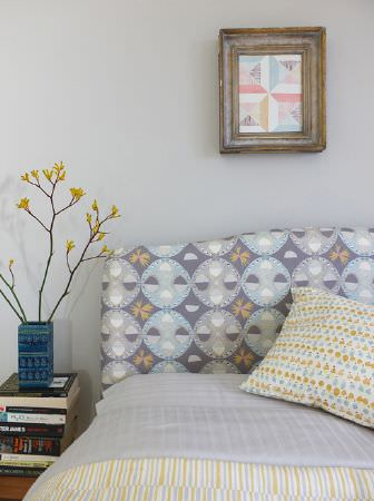 Louise Body -  Peggy Fabric Collection - Light shades of grey, yellow and white making up patterned bedding, cushions and a headboard, beside a stack of books