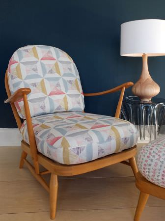 Louise Body -  Peggy Fabric Collection - Low wooden chair with seat and back cushions made with a pastel geometric print, with a footstool, clear table and a lamp