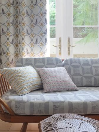 Louise Body -  Peggy Fabric Collection - Patterned and dotted seat and scatter cushions made in pale colours on a wood sofa, with long curtains and a carved wood table