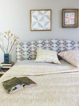 Louise Body -  Peggy Fabric Collection - Bed with a grey, white and green patterned headboard, bedding and cushions, with books, a vase and a framed picture