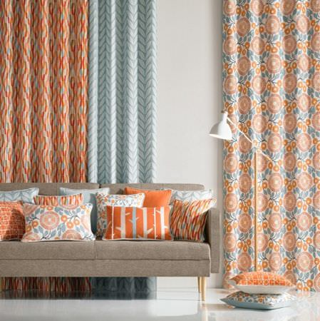 Natasha Marshall -  Alegre Fabric Collection - Various different patterns on 3 orange, light blue and white curtains and 12 scatter cushions, with a plain sofa and lamp