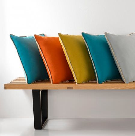 Natasha Marshall -  Alibi Woven Fabric Collection - A simple wood and black metal benchwith 5 plain square scatter cushions in aqua blue, orange, green-gold and light grey