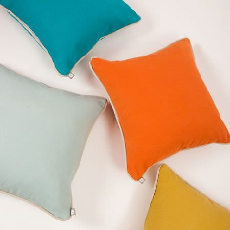 Natasha Marshall -  Alibi Woven Fabric Collection - Four plain aquamarine, orange, light gold and pale grey square scatter cushions lying on a bright white floor