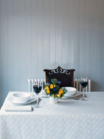 Ochre and Ocre -  Ochre and Ocre Fabric Collection - A white radiator and a black chair behind a table with a white tablecloth, white crockery and black and clear wine glasses