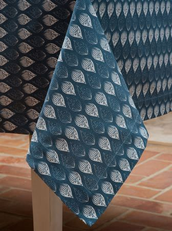 Ochre and Ocre -  Ochre and Ocre Fabric Collection - A tablecloth made from dusky blue and white teardrop patterned fabric, on a light wood table, on a terracotta tiled floor
