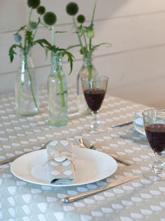 Ochre and Ocre -  Ochre and Ocre Fabric Collection - A pale grey and white teardrop patterned tablecloth and napkin, white crockery, clear wine glasses, and glass bottle vases