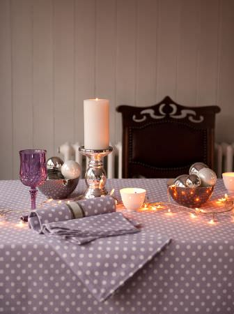 Ochre and Ocre -  Ochre and Ocre Fabric Collection - A black chair with a lilac and white polka dot tablecloth and napkin, silver ornaments and a candlestick, and a purple glass