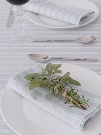 Ochre and Ocre -  Ochre and Ocre Fabric Collection - Sprigs of herbs, white plates, silver spoons, and a tablecloth and napkins made from pale grey and white striped fabrics