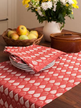 Ochre and Ocre -  Ochre and Ocre Fabric Collection - Red and white teardrop patterned napkins and a table runner on a wooden table with white plates, a jug, bowls and fruit