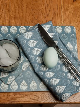Ochre and Ocre -  Ochre and Ocre Fabric Collection - A duck egg blue egg, a knife, a glass, and napkins made from blue and white teardrop patterned fabric, on a wood table