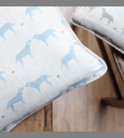 Olive and Daisy -  Olive and Daisy Fabric Collection - Two dog print cushions featuring small, simple light blue and grey designs and dots on plain white backgrounds