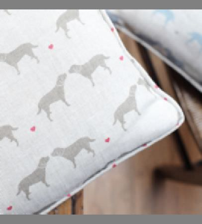 Olive and Daisy -  Olive and Daisy Fabric Collection - Small pink hearts and light grey dog silhouettes printed on a chalk white coloured cushion, with a blue and grey cushion