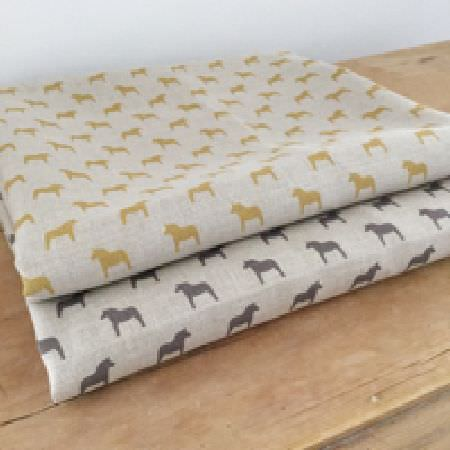 Olive and Daisy -  Olive and Daisy Fabric Collection - Small pony silhouettes printed in gold and charcoal colours on two folds of pale grey fabric, placed on a wooden surface