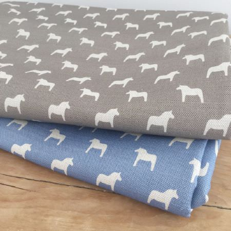 Olive and Daisy -  Olive and Daisy Fabric Collection - A wooden surface with two folded pony print fabrics, made with a white design on iron grey and cobalt blue backgrounds