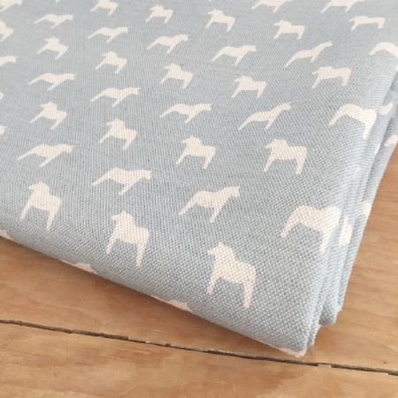 Olive and Daisy -  Olive and Daisy Fabric Collection - Pony print fabric with a small, simple white silhouette design on a light blue background, folded on a wooden surface