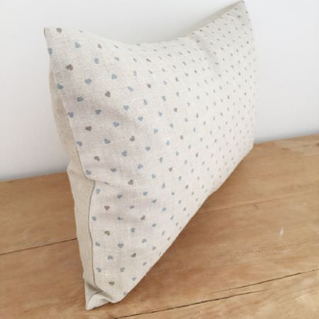 Olive and Daisy -  Olive and Daisy Fabric Collection - A rectangular cushion with plain beige on one side and a small heart print on the other, made in light shades of grey