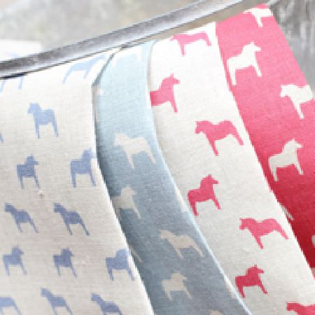Olive and Daisy -  Olive and Daisy Fabric Collection - 4 fabrics draped over a metal bucket, all made with small, simple pony prints in white, light blue and hot pink colours