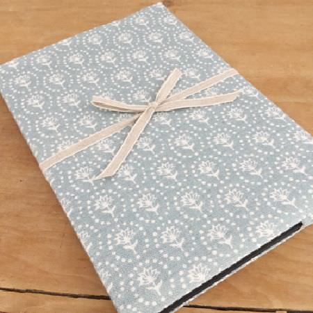 Olive and Daisy -  Olive and Daisy Fabric Collection - A piece of light blue fabric printed with simple white flowers and dots arranged in circles, tied with plain beige ribbon