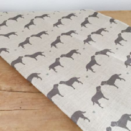 Olive and Daisy -  Olive and Daisy Fabric Collection - Graphite grey coloured dogs printed in a simple design on a piece of off-white fabric, draped over a wooden surface