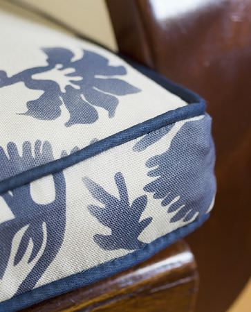 Olivia Bard -  Curious World Fabric Collection - Stuffed white seating pillow with navy blue borders and a pattern of flowers and leaves in the same colour