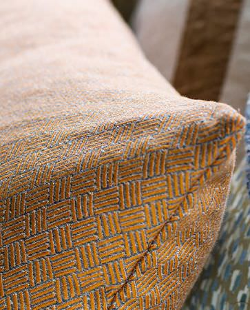 Olivia Bard -  Curious World Fabric Collection - Grey cushion from Curious World fabric collection featuring dominant woven pattern in orange