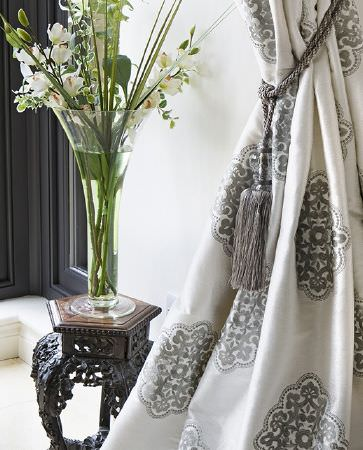 Olivia Bard -  Do Decadence Fabric Collection - Luxurious white curtain decorated with elegant grey floral pattern with a shiny silver tassel tie back